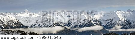 Dramatic Snow Covered Mountains Landscape. Amazing Panoramic Snowy Winter Landscape In Alps At Sunri