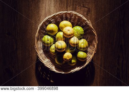 Asian Lime In Bamboo Basket, Sun Shines On Wooden Table,   Light And Shadow.
