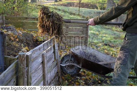 Shuffling Compost For Aeration And Better Rot. The Gardener Uses A Shovel And Pitchfork In His Hand.