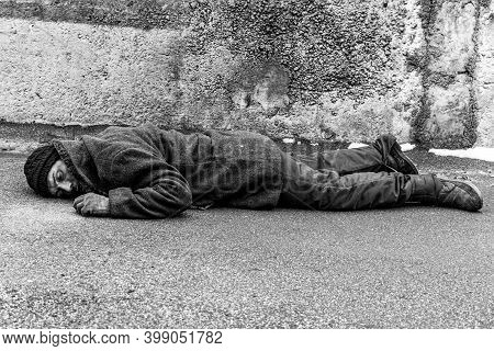 A Dirty Homeless Man Lies On The Asphalt. A Homeless Man In Warm Clothes Lies With His Face To The G