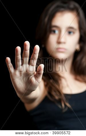 Hispanic girl with her hand extended signaling to stop useful to campaign against violence, gender or sexual discrimination (image focused on her hand)