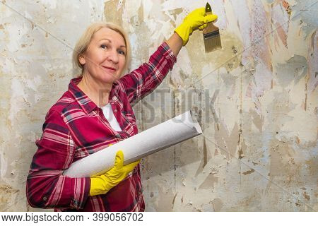 The Woman Is About To Cover The Decrepit Wall With Wallpaper. Diy Repair.