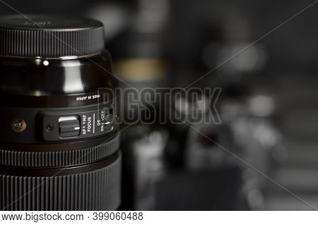 Sigma 24-105 F4 Art Lens With Canon Eos R Photocamera And Other Canon Lenses On Black Wooden Table.