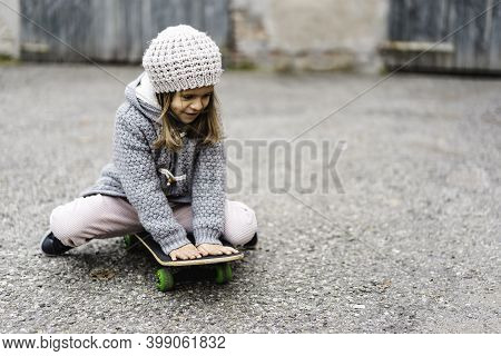 Adorable Little Girl In Winter Wool Clothes Sitting On Skateboard Outdoors In Backyard - Smiling Lit