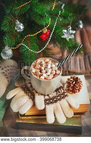 Christmas Still Life. A Mug Of Hot Coffee With Marshmallows Are On A Stack Of Books With Gloves And