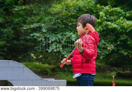 Outdoor Portrait Active Kid Playing Mini Golf In The Park, Cute  Boy Playing Crazy Golf In The Park,