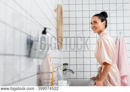 Side View Of Woman Smiling At Camera Near Sink And Toiletries On Blurred Foreground In Bathroom