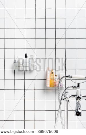 Toiletries Near Faucet On Blurred Foreground In Modern White Bathroom, Stock Image
