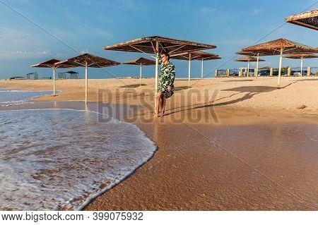 Girl In White Dress With Green Leaves Posing On The Beach Near Sun Umbrella. Girl In Dress Posing On