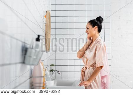 Woman Smiling While Looking At Mirror Near Toiletries On Blurred Foreground