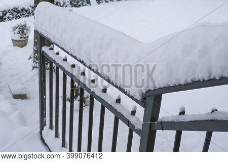 Snow Covered Black Metal Handrail By The House Across Snowy Backyard. Winter Season