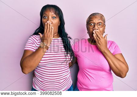 Hispanic family of mother and daughter hugging together with love covering mouth with hand, shocked and afraid for mistake. surprised expression
