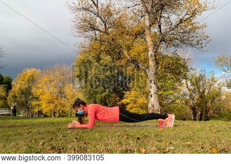 Sporty Dressed Woman Doing The Plank On A Mat In The Park Wearing A Mask To Protect Herself From The