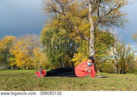 Woman Dressed In Sportswear Lying On A Mat In The Park Wearing A Mask To Protect Herself From The Co