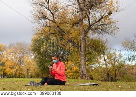 Woman Dressed In Sport Sitting On A Mat In The Park Wearing A Mask To Protect Herself From The Coron