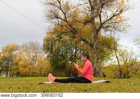 Sporty Dressed Woman Sitting With Legs Stretched Out On A Mat In The Park Wearing A Mask To Protect