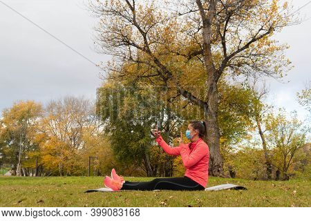 Sporty Dressed Woman Sitting With Her Legs Stretched Out On A Mat In The Park Wearing A Mask To Prot