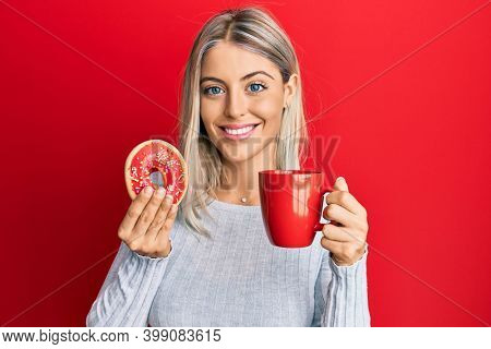 Beautiful blonde woman eating doughnut and drinking coffee smiling with a happy and cool smile on face. showing teeth.