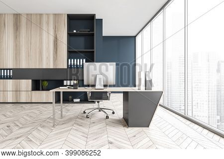 Blue And Wooden Light Office With Big Shelf, Chair And Table With Computer, On Parquet Floor Near Wi