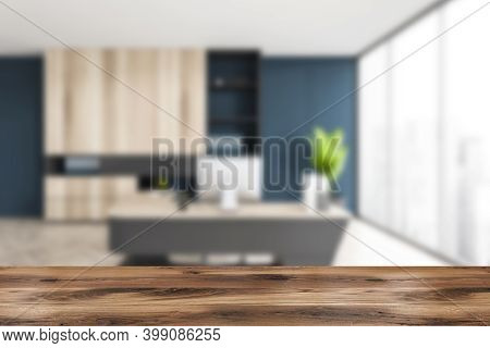 Wooden Desk Foreground On Blurred Background Of Luxury Light Office With Big Shelf, Chair And Table