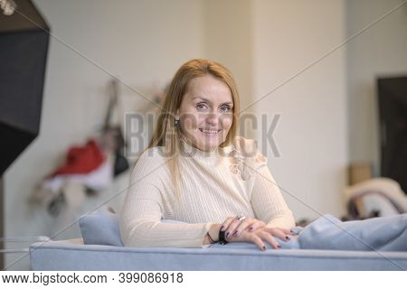 Smiling Happy Woman At Home. Smiling Middle-aged Blond Woman With A Beaming Smile Sitting On A Sofa