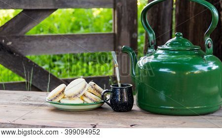 Mate And Kettle With A Plate Of Alfajores And Yerba Mate Infusion In The Argentine Countryside