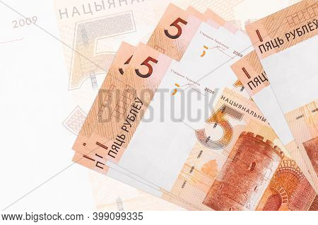 5 Belorussian Rubles Bills Lies In Stack On Background Of Big Semi-transparent Banknote. Abstract Pr