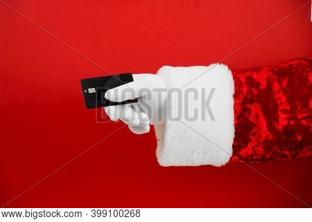 Santa Claus Hand Holding Blank Black Plastic Credit Card On Red Background With Clipping Path. Shopp