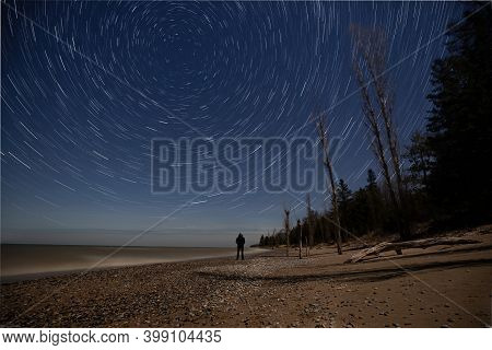 Person Watching The Stars With Star Trail Effect On A Beach, Near Southampton, Ontario