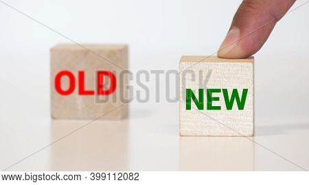 Man Hand Picking Wooden Cubes With The Text New Over Wooden Cubes With The Text Old
