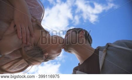 Amorous Couple Kissing On A Background Of Blue Sky.