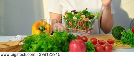 Close-up Of Woman Hands Showing Salad Bowl And Various Green Leafy Vegetables On The Table At The Ho
