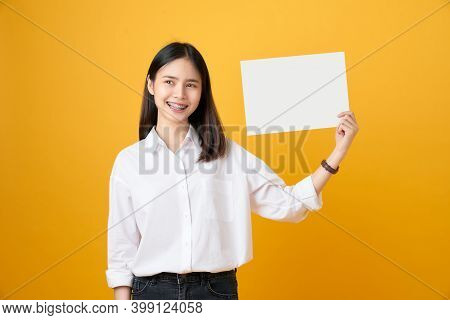 Young Asian Woman Holding Blank Paper With Smiling Face And Looking On The Yellow Background. For Ad