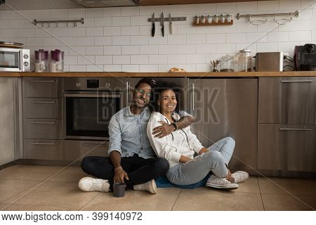 Portrait Of Smiling Biracial Couple Renters Relax In Kitchen
