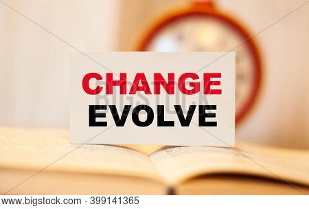 Text On White Paper Change Evolve, On Open Book.
