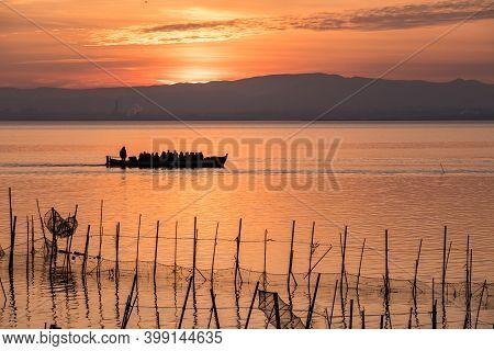 Albufera Sunset Tourist Ride Boat Orange Sky At Lake Natural Park Valencia Spain, Traditional Fishin