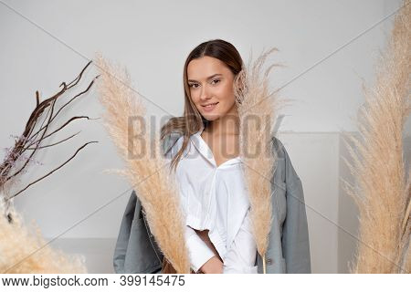 Young Brunette In A White Shirt, A Stylish And Concise Portrait In Light Colors, A Dry Spikelet In H