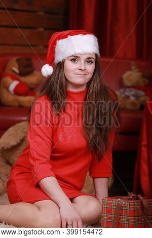 Portrait Of A Young Woman In Santa Helper Hat Ad Red Dress In Pr