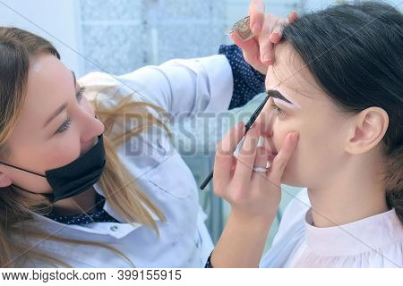 Cosmetologist Is Tinting Woman Eyebrows With Brown Paint In Beauty Clinic, Side View. Beautician App