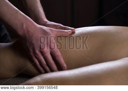 Massagist Man Scrubbing Womans Legs Natural Scrub In Spa Salon, Hands Closeup. Procedure Of Peeling