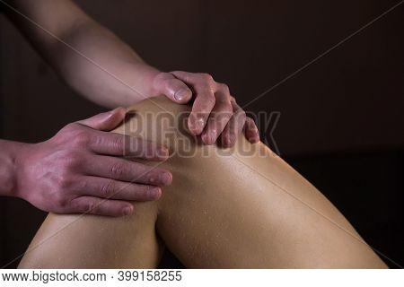Massagist Scrubbing Womans Knee And Legs Natural Scrub In Spa Salon, Closeup Hands. Procedure Of Pee