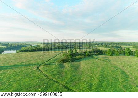 Flying Over Green Field Forest And River At Sunset At Summer Day On Nature On Beautiful Place. Aeria