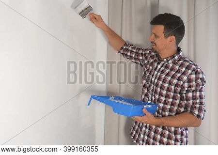 Man House Painter Is Painting Wall In Grey Using Brush Doing Renovation At Home, Side View. Diy Proj