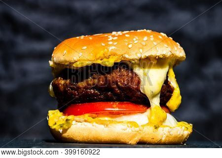 Close Up Of Homemade Cheeseburger With Onion Rings, Melted Cheese, Pickles, Tomatoes.
