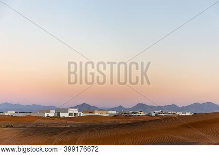 Landscape View Of Desert In United Emirates With Local Al Madam Ghost Village And Hajar Mountains In