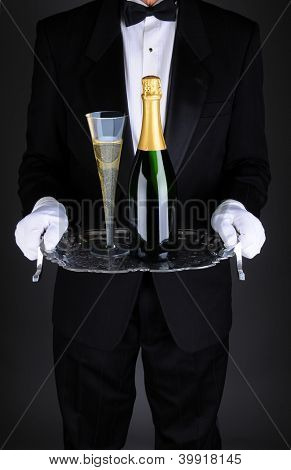Closeup of a waiter with a bottle and flue of champagne on a silver serving tray. Vertical format over a light to dark gray background. Man is unrecognizable.