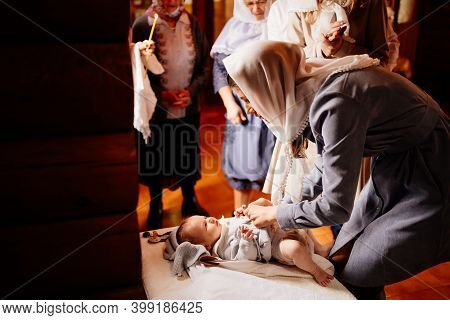 Mom Dress Their Child In The Church On A Table. The Ordinance Of Baptism.
