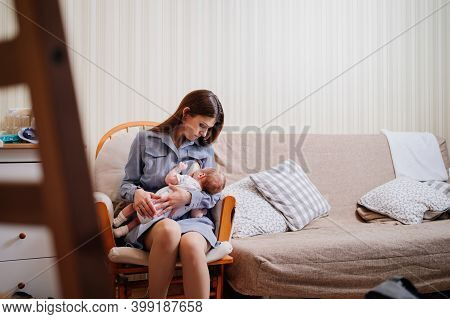 Mother Breastfeeds A Newborn At Home On The Couch. The Benefits Of Breastfeeding
