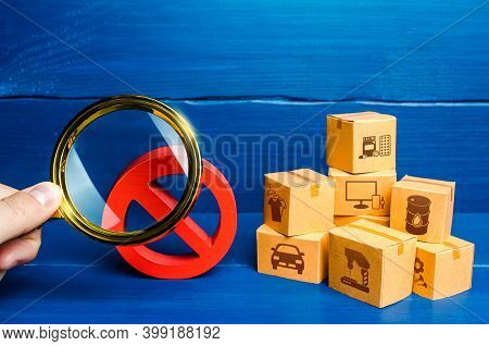 Man With A Magnifying Glass Examines Red Prohibition Sign No Near Boxes. Assessment Of Damage From S
