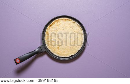 Top View With A French Pancake Freshly Baked In A Cast Iron Pan On A Purple Background. Making Crepe